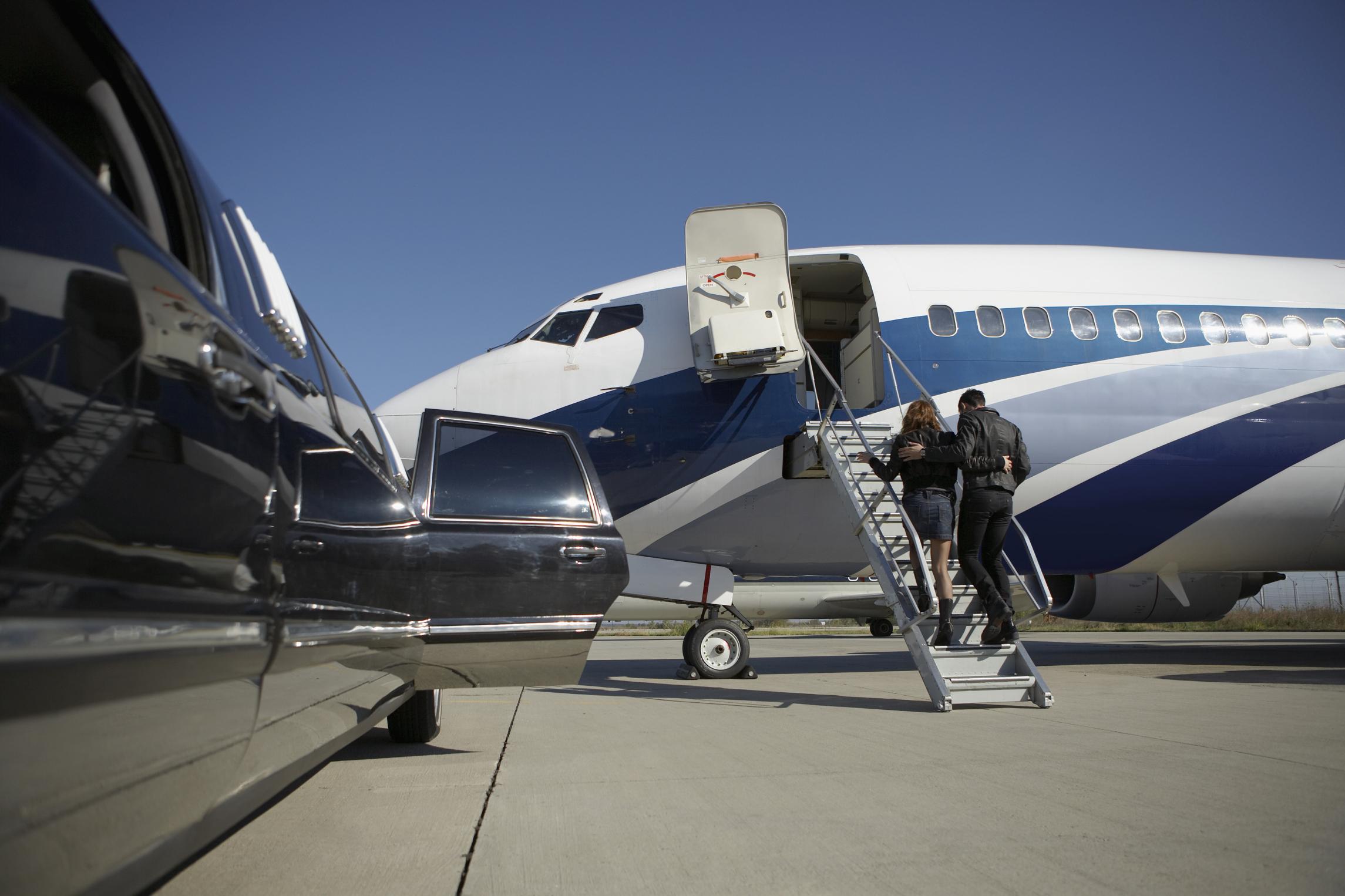 Passengers boarding airplane on runway
